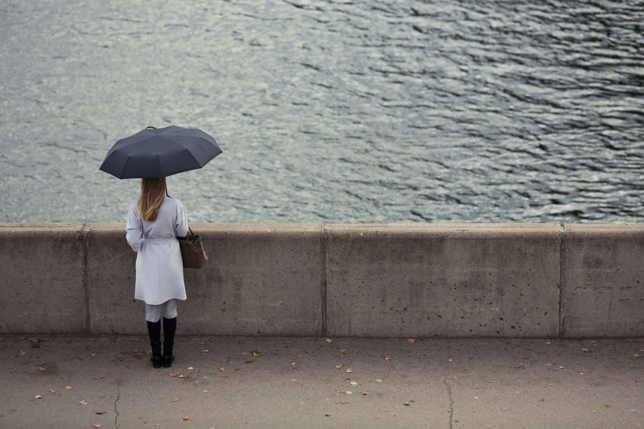 Lonely girl with an umbrella. Sad autumn day.